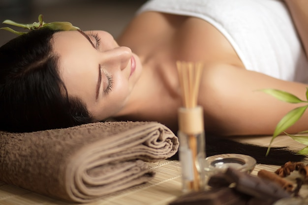 Pretty woman laying in spa salon with closed eyes and relaxed Premium Photo