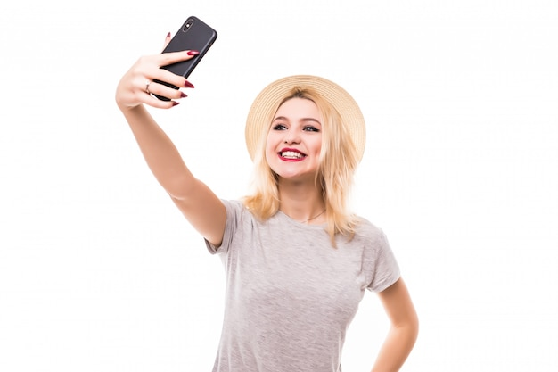 Pretty woman make a duck face and takes a selfie with her smartphone Free Photo