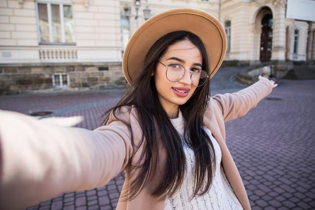 예쁜 여자는 화창한 날에 도시에서 야외에서 그녀의 새로운 스마트 폰에 셀카를 만들 무료 사진