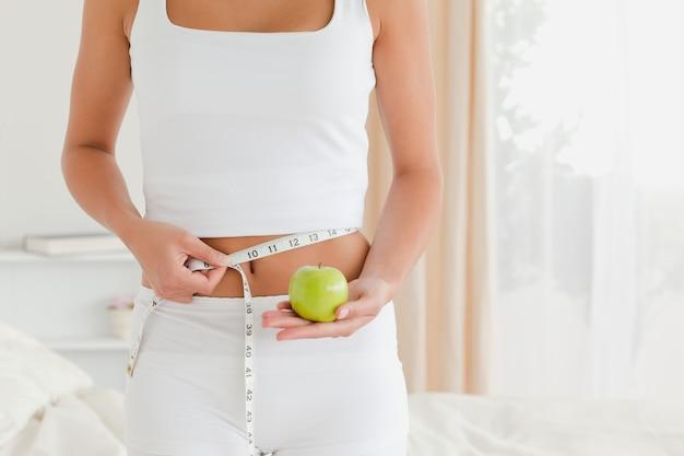 Pretty woman measuring her waist while holding an apple Premium Photo