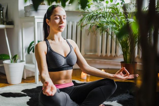 Pretty woman meditating at home Free Photo