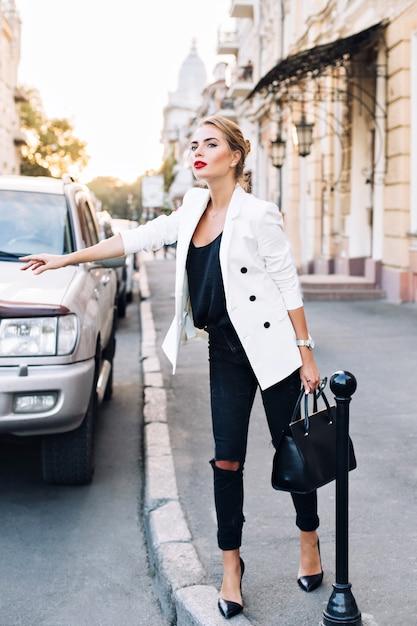 Красивая женщина на каблуках ловит такси в городе. она держит в руке сумку. Бесплатные Фотографии