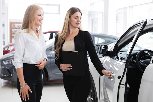 Pretty woman opening the car door Free Photo