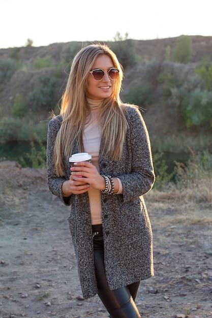 朝のコーヒーと屋外のきれいな女性 Premium写真