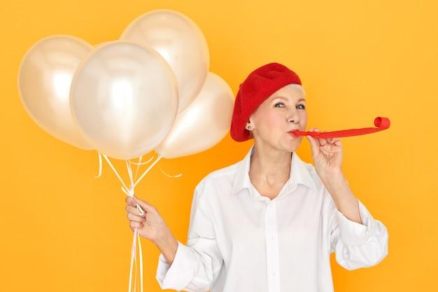 パーティーを楽しんでいる赤いボンネットのきれいな女性年金受給者、笛を吹く彼女の孫を楽しませ、白いヘリウム気球を持って 無料写真