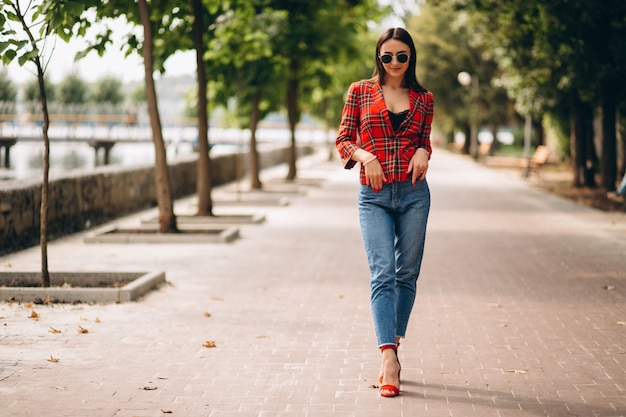Pretty woman in red jacket outside in park Free Photo