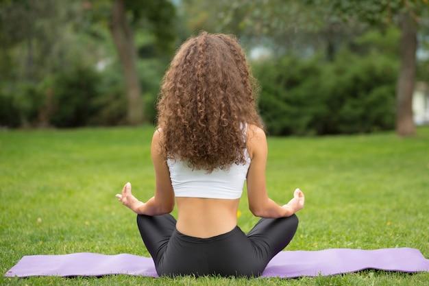Donna graziosa che si siede indietro facendo meditazione yoga Foto Gratuite