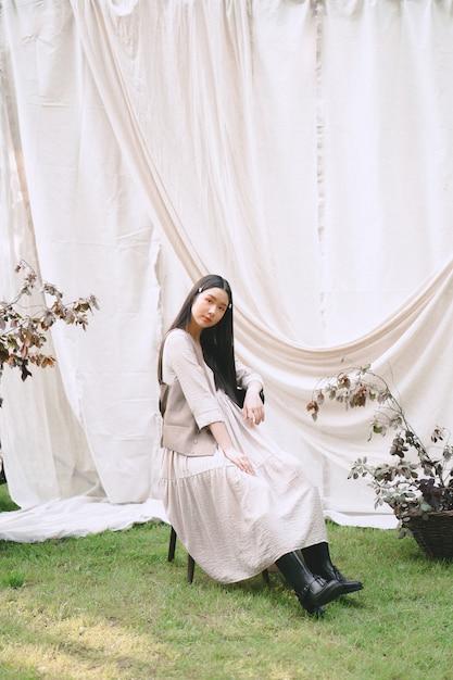椅子に座って、庭で探しているきれいな女性 無料写真