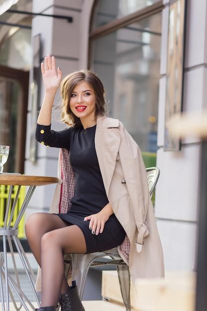 Bella donna seduta nella caffetteria all'aperto e in attesa di amici Foto Gratuite