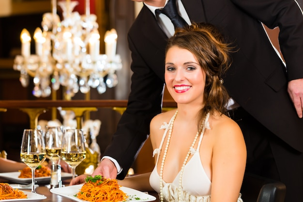 Pretty woman sitting at a table in a fine dining restaurant, waiter served the dinner, a large chandelier is in Premium Photo