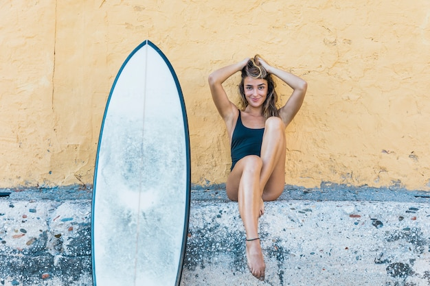 Pretty woman sitting with surfboard leaning on wall Free Photo