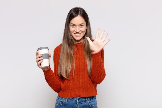 笑顔でフレンドリーに見えるきれいな女性、前に手を前に5番または5番を示し、カウントダウン Premium写真