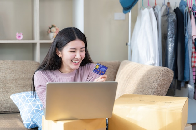 Pretty woman smiling and looking to credit card in hand Free Photo