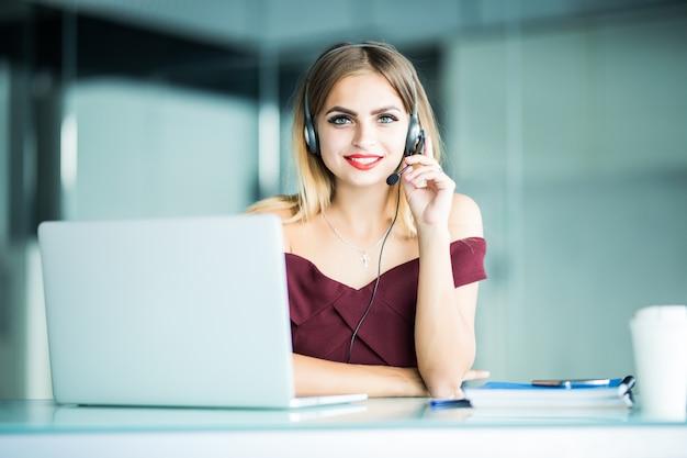 Operatore del centro di supporto donna graziosa con auricolare in ufficio Foto Gratuite
