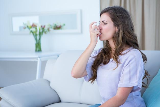Pretty woman taking her inhaler Premium Photo