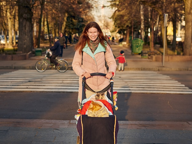 Pretty woman walking in city park with a cats in blanket sitting in baby cariage Premium Photo