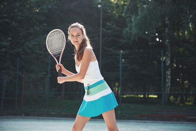 A pretty woman wearing a sportswear tennis court on the court. Free Photo