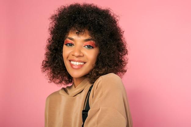 Bella donna con pelle nera e acconciatura africana alla moda in abito sportivo in posa sul rosa Foto Gratuite