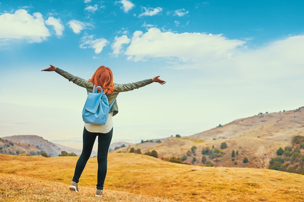 Pretty woman with blue backpack outdoors enjoying nature mountains Premium Photo