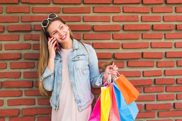 Красивая женщина с красочными сумок, разговаривает по телефону на кирпичной стене Бесплатные Фотографии