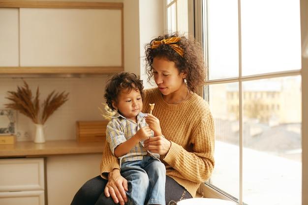 ひざの上に愛らしい赤ちゃんと一緒に窓辺に座っている巻き毛のきれいな女性は、彼におもちゃやキャンディーを与え、興味と好奇心を持って見ている小さな子供。母性、育児、一体感 無料写真