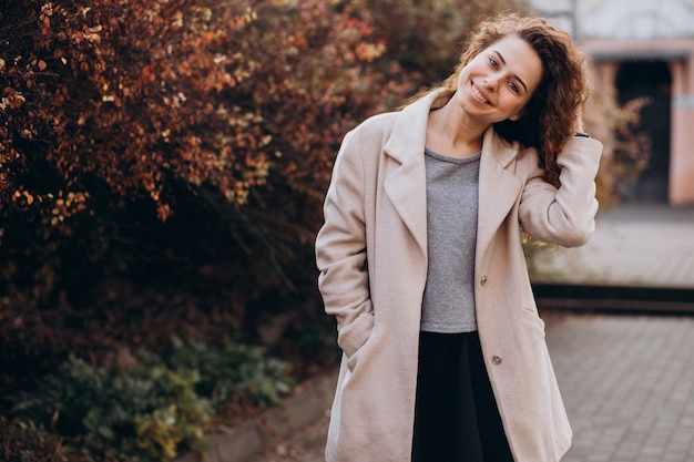 Pretty woman with curly hair walking in an autumn coat Free Photo