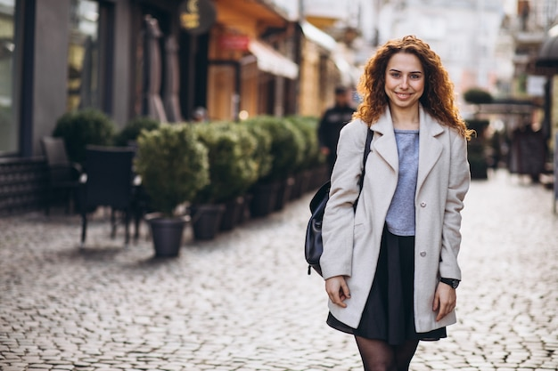 Pretty woman with curly hair walking at a cafe street Free Photo