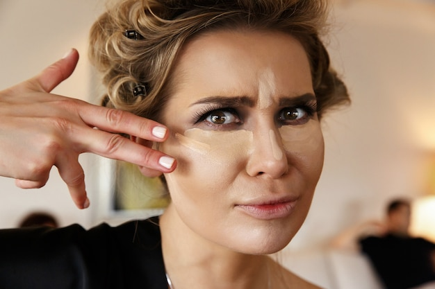 Pretty woman with dark smokey eyes makeup and highlighter under eyes and on the nose Free