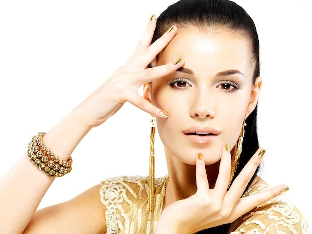 Красивая женщина с золотыми гвоздями и красивыми золотыми украшениями, изолированными на белой стене Бесплатные Фотографии