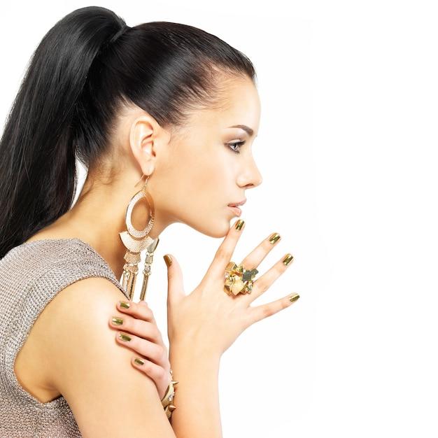 Bella donna con chiodi d'oro e splendidi gioielli in oro isolati su bianco Foto Gratuite
