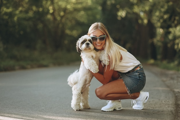 Pretty woman with her dog out in the park Free Photo