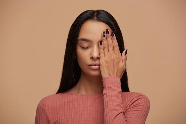 La bella donna con gli occhi chiusi nasconde metà del viso con il palmo della mano, mostra una bella manicure Foto Gratuite