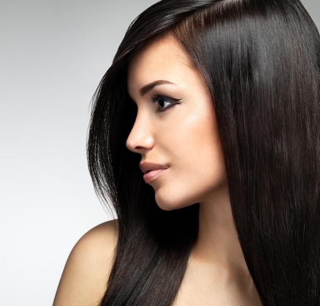 긴 갈색 머리카락을 가진 예쁜 여자. 패션 모델 포즈의 프로필 초상화 무료 사진