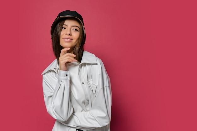 완벽 한 미소와 예쁜 여자 세련 된 모자와 분홍색 배경에 포즈 흰색 재킷을 입고. 격리. 무료 사진