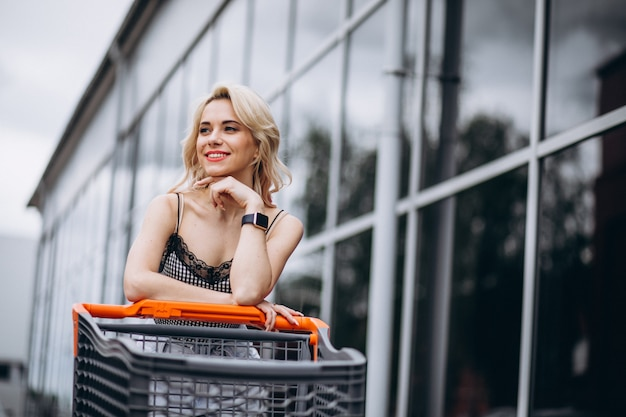 Pretty woman with shopping cart outside Free Photo