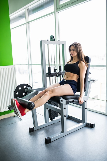 Pretty woman working her quads at machine press in the gym Free Photo