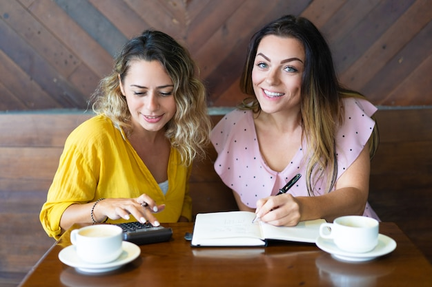 Pretty women drinking coffee and using calculator in cafe Free Photo