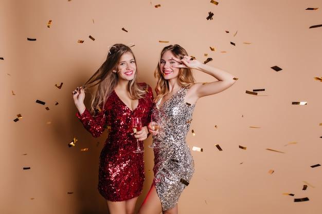 Красивые женщины в модных блестящих платьях веселятся на девичнике и пьют вино Бесплатные Фотографии