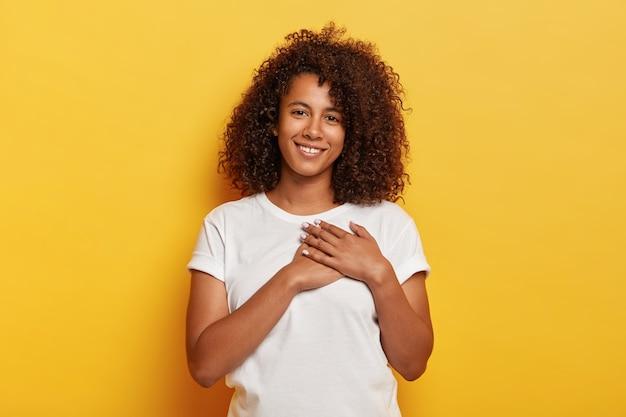 かなり若いアフリカ系アメリカ人の女性が手のひらを心臓の近くに保ち、感謝の気持ちを表します 無料写真