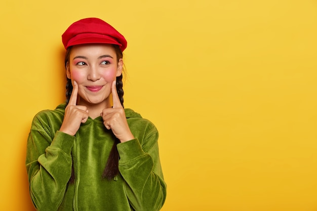Pretty young asian model keeps both fore fingers on cheeks, looks with dreamy expression aside, has minimal makeup, wears red beret, green velvet hoodie Free Photo