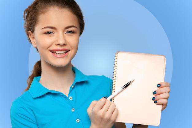 Pretty young beautiful woman standing, writing, take notes Premium Photo