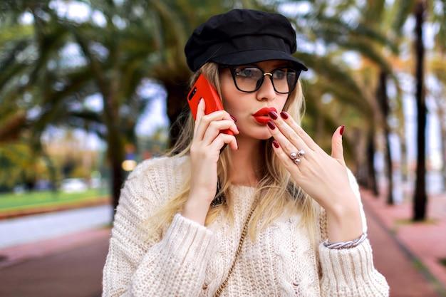 Довольно молодая блондинка разговаривает по телефону, элегантный повседневный наряд, шляпа, свитер и прозрачные очки, положительные эмоции, пальмы вокруг. Бесплатные Фотографии