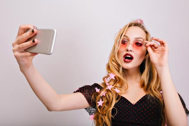 かなり若いブロンドの女性がパーティーでselfieを取って、開いた口でセクシーに見える。ピンクのおしゃれなメガネ、黒いドレスを着て、美しい長い巻き毛を持っています。 無料写真