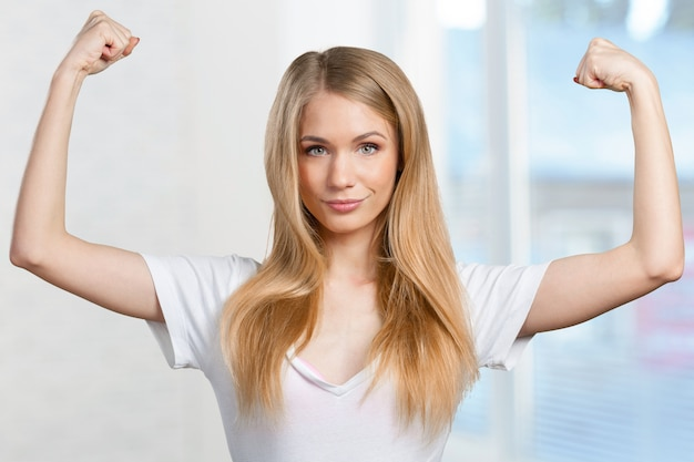 Pretty young blonde woman throwing her arms up into the air in jubilation of her success Premium Photo