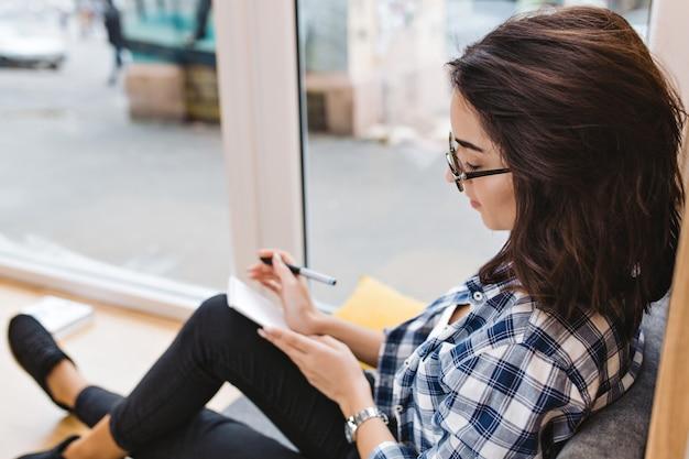 Довольно молодая брюнетка женщина в черных очках, сидя на окне дома, писать в записной книжке. комфортное рабочее место, анализирующий, бодрое настроение, умница. Бесплатные Фотографии