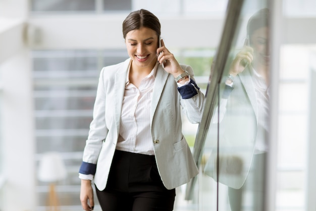 Pretty young business woman stands on the stairs at the office and use mobile phone Premium Photo