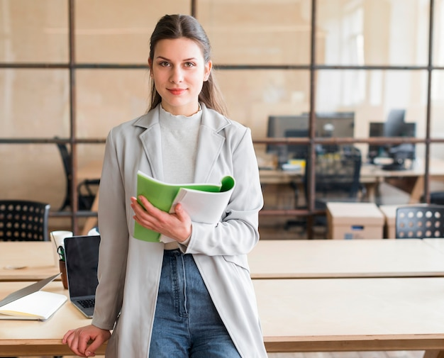 Pretty young businesswoman leaning on desk holding book looking at camera in office Free Photo