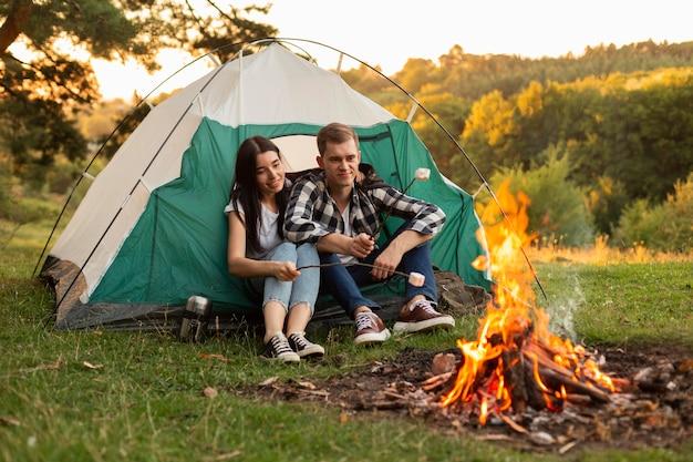 Pretty young couple enjoying bonfire Free Photo