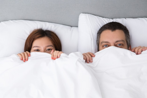 Pretty young couple hiding behind duvet Free Photo