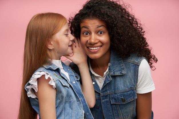 ピンクの秘密の話を聞いている間、鼻ピアスが不思議に見えて、驚くほど眉を上げているかなり若い暗い肌の巻き毛のブルネットの女性 無料写真